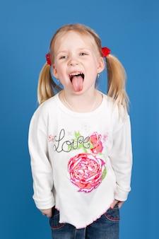 おさげ髪に髪を持つ少女は舌を示しています