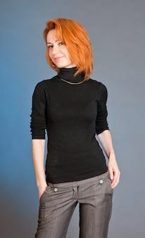 スタジオで赤い髪を持つカジュアルな服装で細身の美しい女性