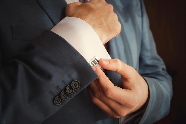 彼がフォーマルな服装に身を包んだようにカフスボタンを身に着けている新郎をクローズアップ