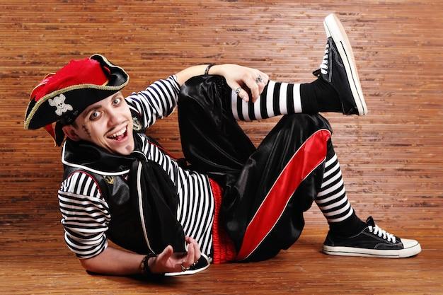 海賊のスーツを着た俳優は床に横たわっています