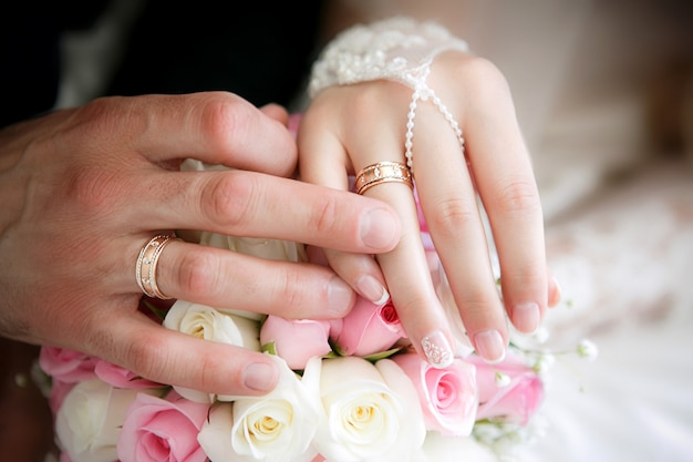 Руки жениха и невесты с обручальными кольцами и свадебный букет из роз