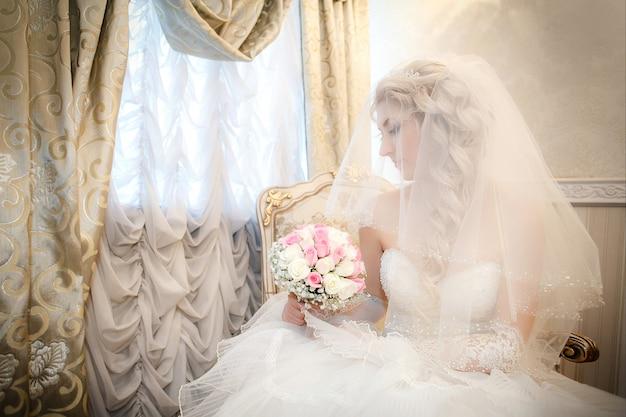 Портрет невесты со свадебным букетом из роз в руке сидит на диване возле окна