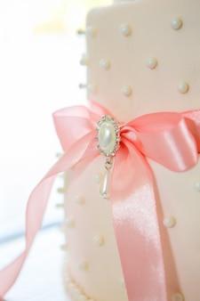 白いアイシングとピンクの弓のウェディングケーキ