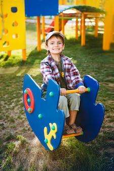 幸せなゲーム-遊び場でキャップのかわいい男の子