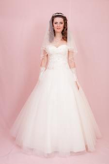 美しい花嫁はウェディングドレスに立っています。