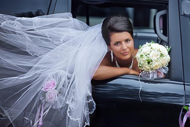 Невеста с развевающейся вуалью смотрит из окна машины