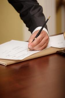 Крупным планом бизнесмена, писать на повестке дня левой рукой