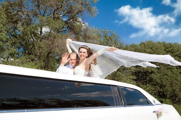 Жених и невеста, стоя в развевающемся лимузине