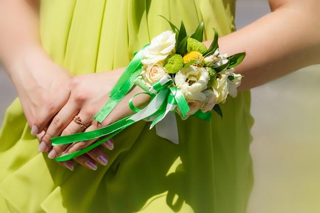 花の色のウェディングブーケを持って花嫁介添人