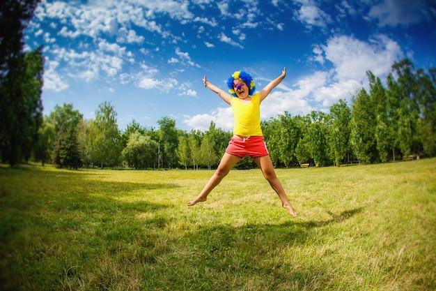 パーティーピエロ青いかつら面白い幸せな開いた腕式と花輪を持つ子供子供の女の子は公園でジャンプしています
