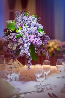 テーブルの上の花瓶にライラックを束します。
