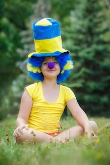女の子は道化師かつらと帽子で草の上に座っています。