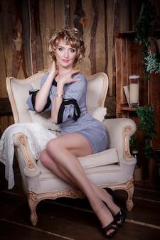 肘掛け椅子に座っている美しい女性