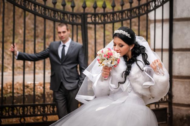 秋の公園で新郎と新婦が鉄の門の近くに立つ