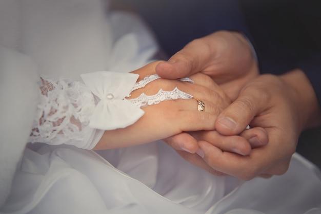 新郎新婦は結婚式のカップルでリング花嫁を着ています。