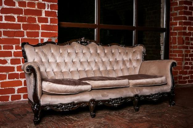 赤レンガの壁にベージュのソファ付きのリビングルーム