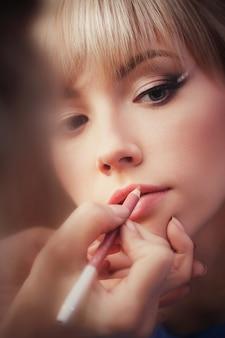 美しい少女は、メイクアップアーティストをクローズアップでメイクを適用します。