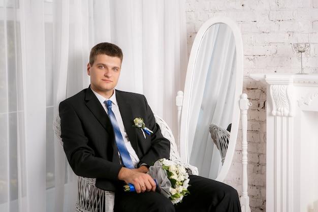 ウェディングブーケを持つ新郎は椅子に座っています。