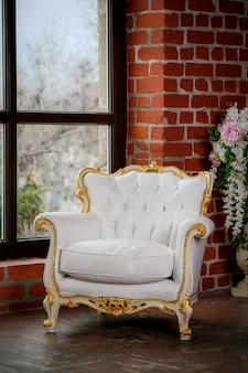 窓の近くの白い革張りのアームチェア