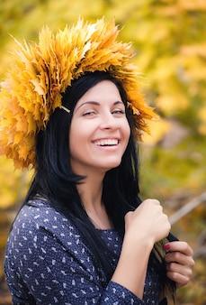 幸せな女は公園で黄色の葉の花輪を着ていた