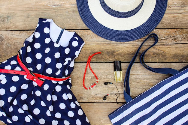 夏服とアクセサリー:ドレス、財布、帽子、ヘッドフォン、香水、ハンドバッグ、古い木製の背景にビーズ。
