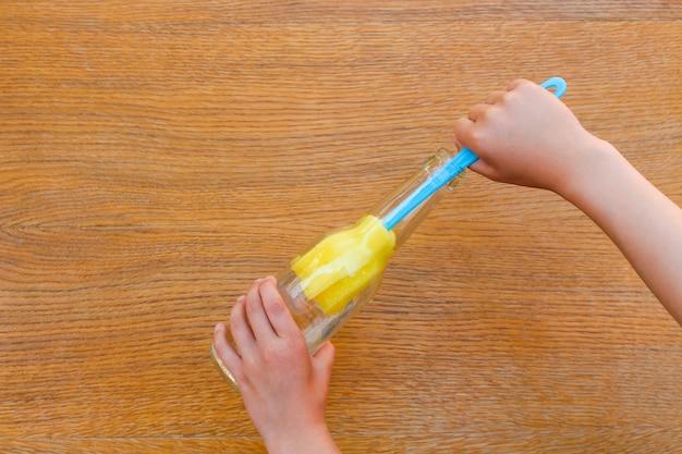 ボトルブラシを洗う女性の手。