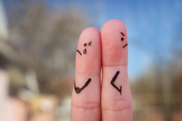 カップルの指アート。さまざまな方向を向いている議論の後のカップル。