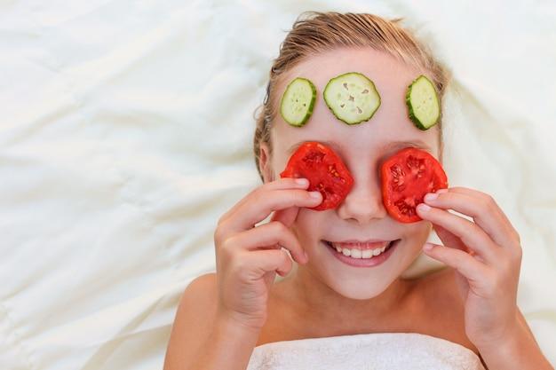 キュウリとトマトの顔のマスクを持つ美しい少女。