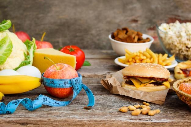 古い木製の背景にファーストフードと健康食品。正しい栄養やジャンクフードを選ぶというコンセプト。