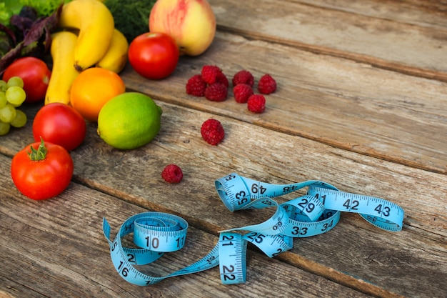 果物、野菜、木製の背景にテープを測定します。