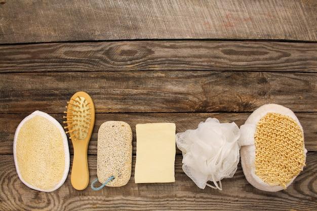 衛生製品:石鹸、くし、スポンジ、軽石石の古い木製の背景。