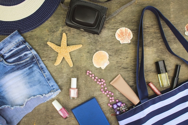 ビーチバッグ、太陽の帽子、化粧品、デニムのショートパンツ、カメラ、古い木製の背景に貝殻。