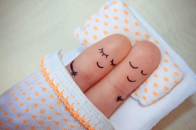 幸せなカップルの指アート。カップルはベッドで眠っています。