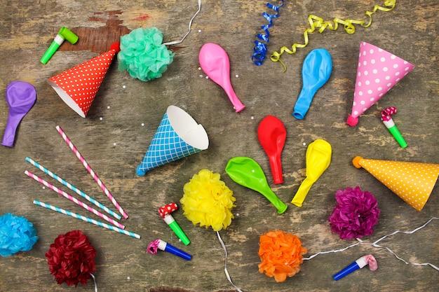 休日の帽子、笛、古い木造の風船。子供の誕生日パーティーのコンセプト上面図。