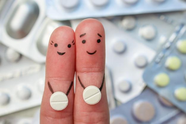 幸せなカップルの指アート。男と女は丸薬を手に保ちます。