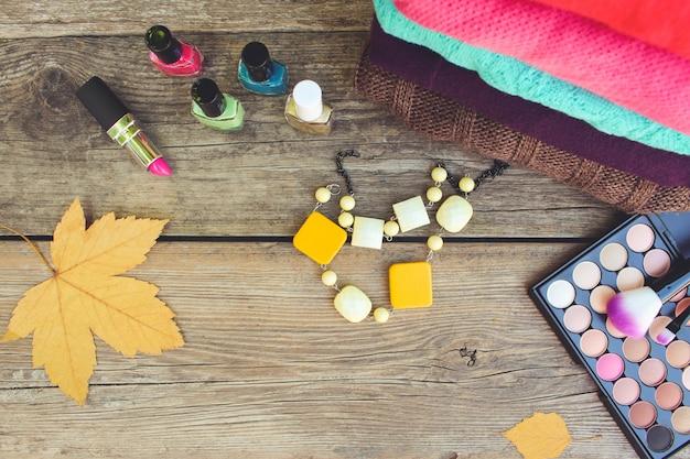 女性の服と木製の背景に化粧品