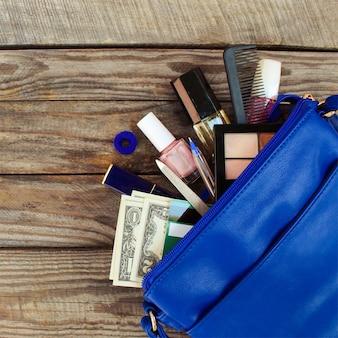 Вещи из открытой дамской сумочки.