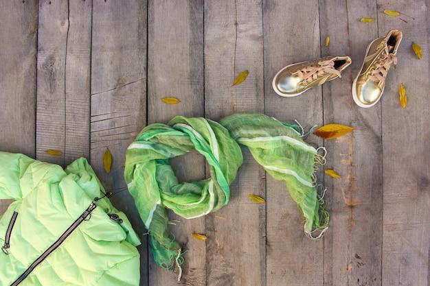 Детская осенняя одежда и желтые листья. вид сверху. квартира лежала.