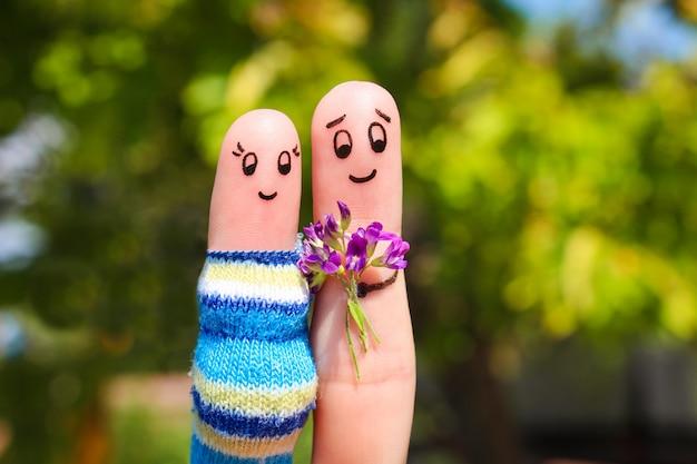 幸せなカップルの指アート。男は花の妊婦を与えています。