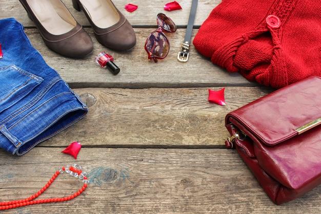 女性の秋服とアクセサリー:赤いセーター、ジーンズ、ハンドバッグ、ビーズ、サングラス、マニキュア、靴、木製の背景のベルト。上面図。