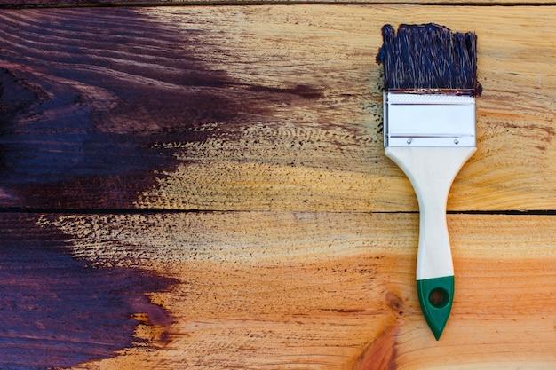 Кисть на деревянных фоне. доска наполовину окрашена.