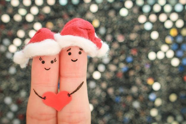 カップルの指アートは新年の帽子でクリスマスを祝います