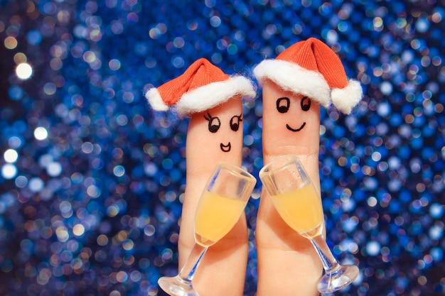 新年の帽子で幸せなカップルの指アート。