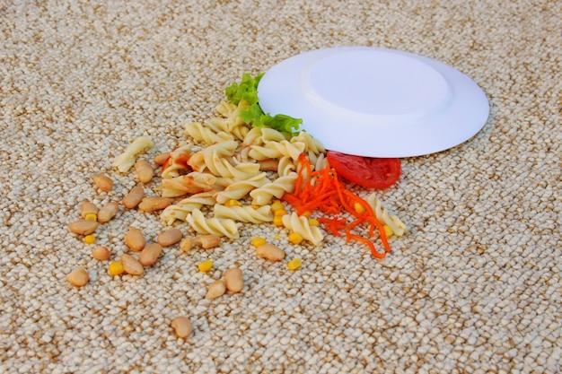 Тарелка с едой упала на бежевый ковер.