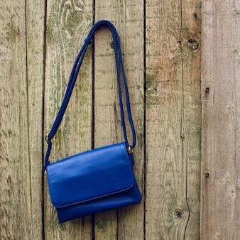 Синяя женская сумочка висит на гвозде на старых деревянных фоне