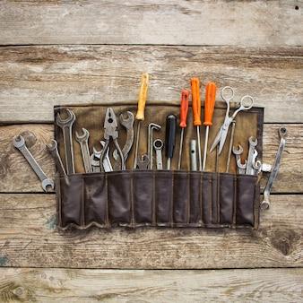 Старые инструменты в сумке на деревянной предпосылке. вид сверху.