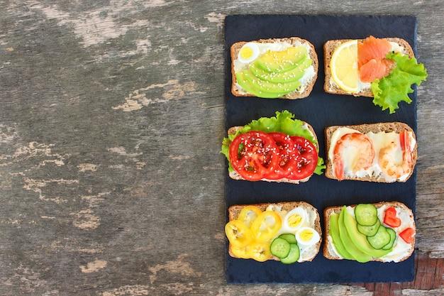 Различные бутерброды на старых деревянных фоне. вид сверху. квартира лежала.