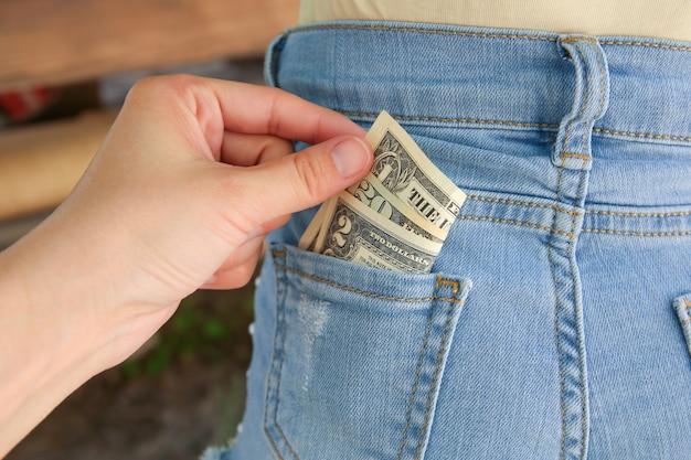 ポケットからお金を盗む泥棒のクローズアップ。