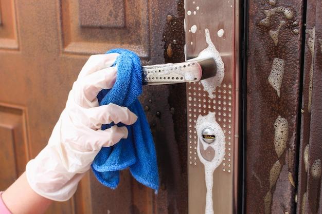 玄関のハンドルを洗う人。
