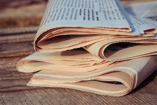古い木材の背景上の新聞。